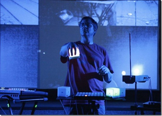 "Playing the song ""I Can See Them"" live.  I'm controlling 4 dimensions of at the same time. Visuals behind me are by artists Project Ruori who are processing a live camera feed. Photo by Hong Waltzer."